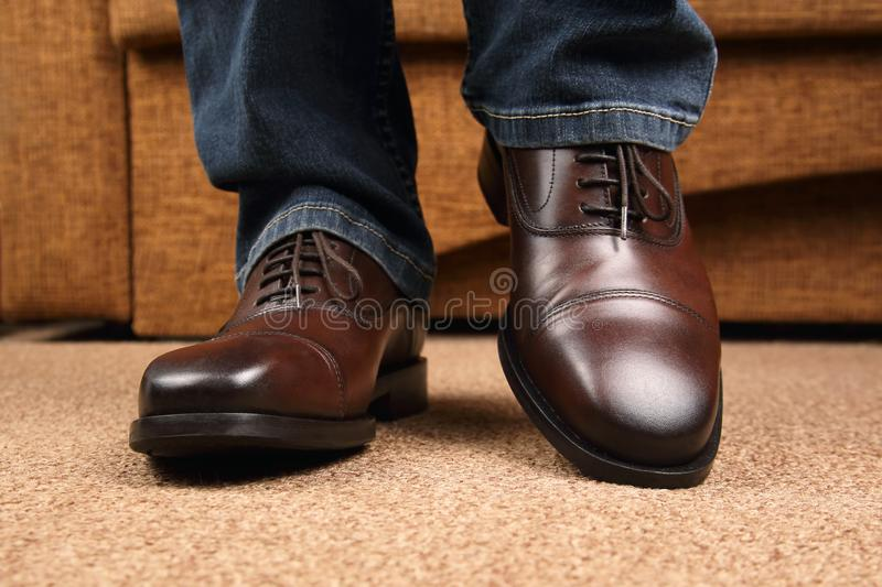Men`s legs in jeans shod in classic brown Oxford shoes. The Men`s legs in jeans shod in classic brown Oxford shoes royalty free stock photo