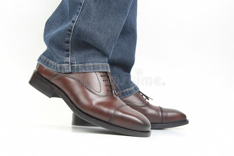 Men`s legs in jeans shod in classic brown shoes. The Men`s legs in jeans shod in classic brown shoes royalty free stock image