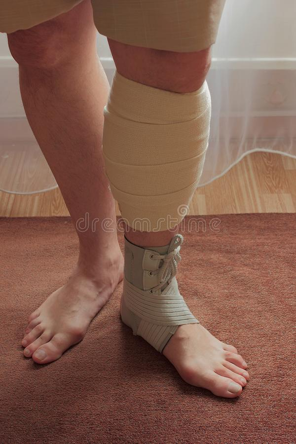 Men`s legs in orthosis and elastic bandage royalty free stock photos