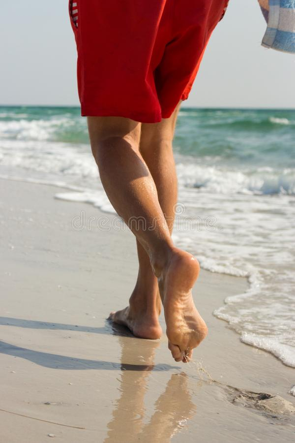 Men`s legs in red shorts at the seaside on sunny summer day. Man walking along white sand beach and blue water ocean. stock photos