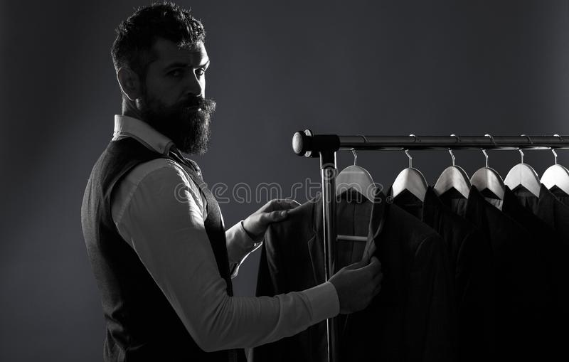 Men`s lothing, shopping in boutiques. Tailor, tailoring. Man suit, tailor in his workshop. Elegant man`s suits hanging royalty free stock image