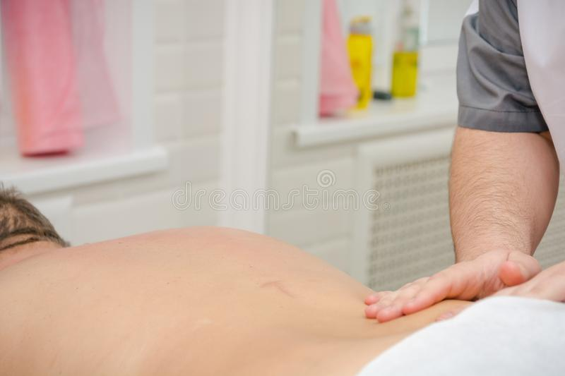 Men`s massage. The man does massage. Massage by hands. Massage in beauty shop royalty free stock image