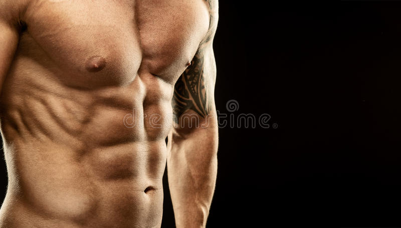 Men's muscular abdomen - close-up - on black background.  stock photo