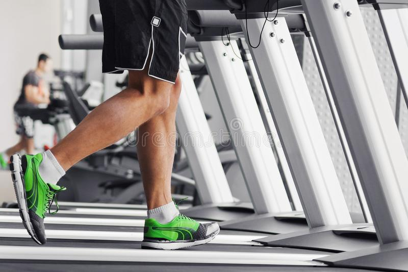 Men`s muscular legs on a treadmill close-up royalty free stock photography