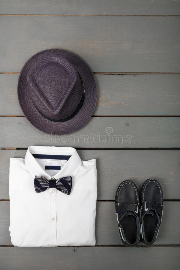 Men's outfit on wooden background. Kids fashion clothes. Grey fedora, white shirt, black bow tie and boat shoes for boy. Top view. Copy space royalty free stock photo