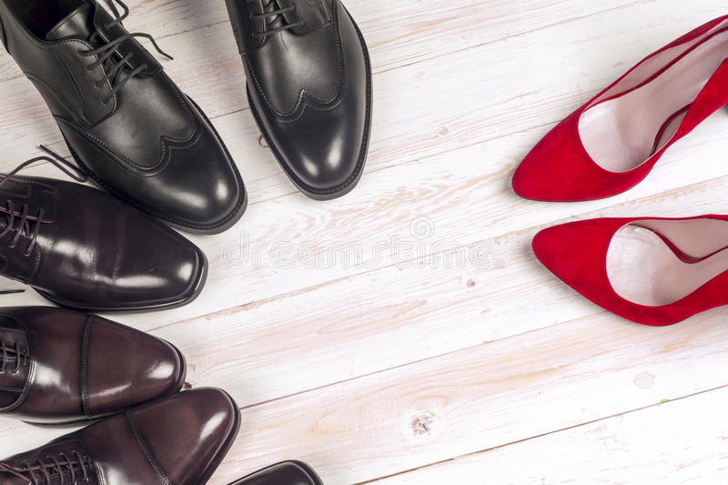 Men`s and red high heel womens shoes on white background. Men`s shoes and red high heel women`s shoes on white background stock images