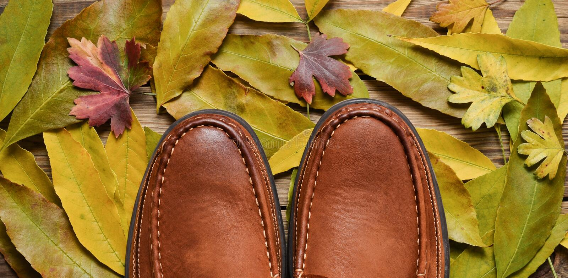Men& x27; s rzemienne kierpec na drewnianej podłoga przeciw tłu spadać kolor żółty opuszczają fotografia royalty free