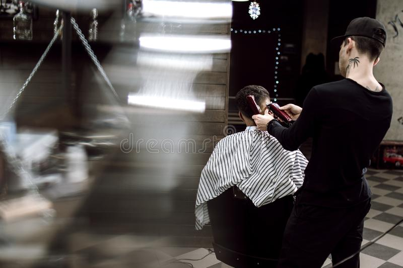 Men`s style. The fashion barber makes a stylish hairstyle for a black-haired man sitting in the armchair in the stylish stock image