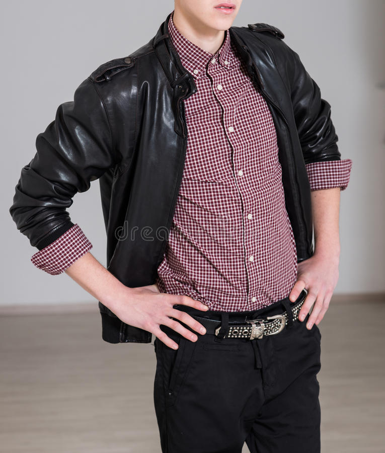 Men`s style. Young fashionable man wearing black leather jacket, denim jeans, checkered shirt and belt stock photography
