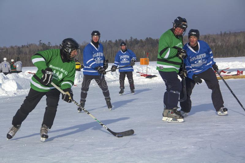 Men`s teams compete in a Pond Hockey Festival in Rangeley. Rangeley, Maine, USA - February 4, 2017:Men`s teams compete on the ice at the 11th annual New England royalty free stock photo