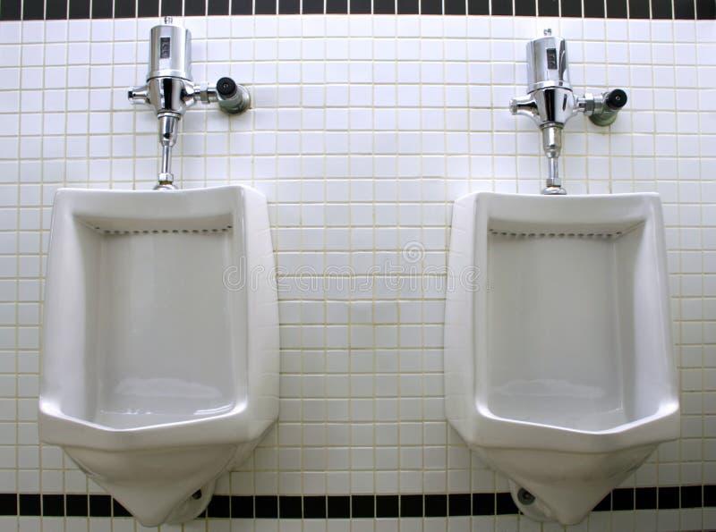Men's Urinals. Utilitarian urinals in a men's toilet stock photo