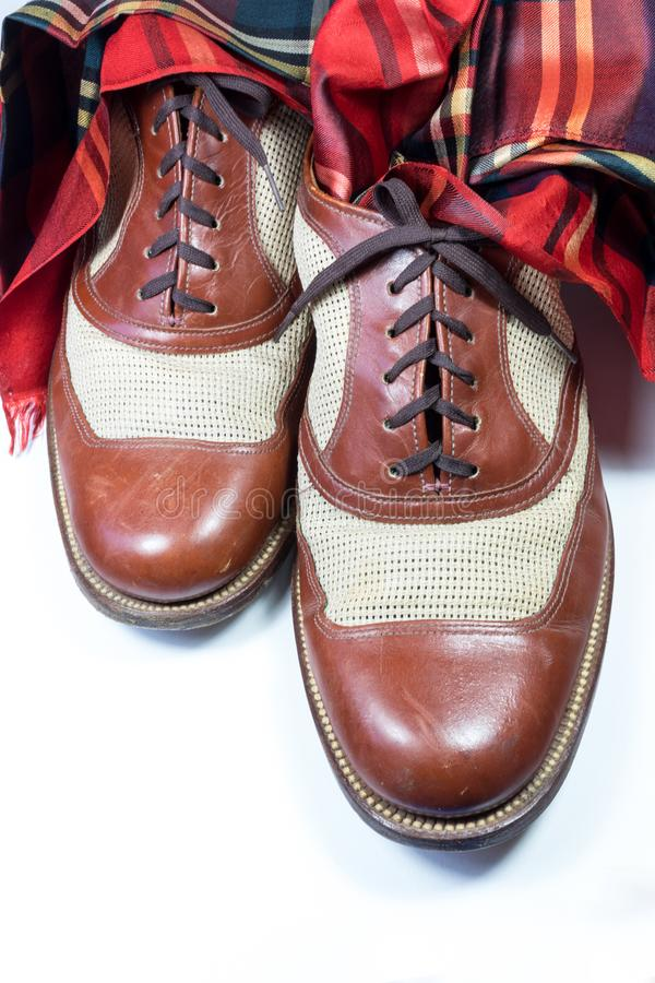 Men`s vintage leather and net shoes with a red plaid silk scarf,. White background, vertical aspect stock photos