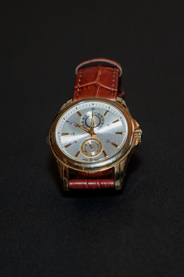 Men`s watch with a brown strap on a black background. / royalty free stock image