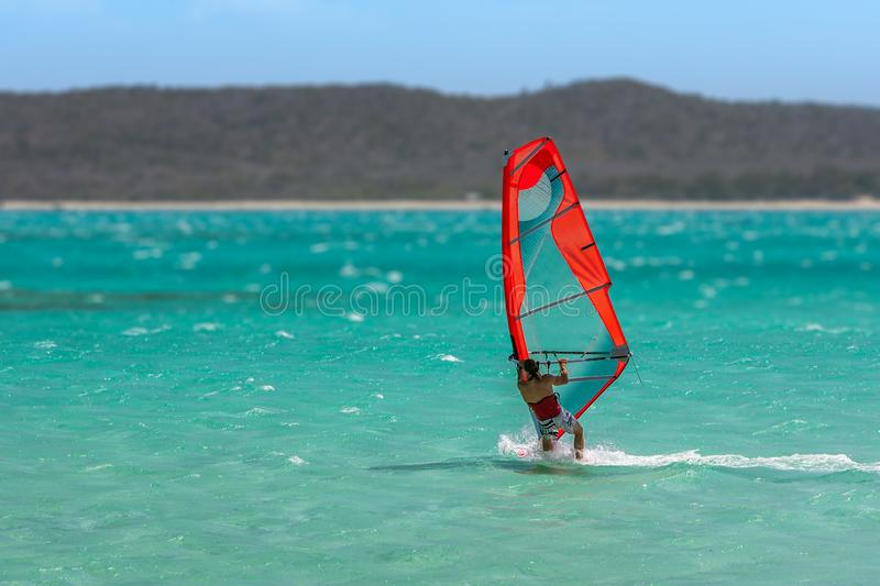 Men& x27;s windsurfer. Surfing in the lagoon, acrobatic, action, active, athletic, bay, beach, coast, dynamic, exotic, extreme, float, focus, freestyle, fun stock images