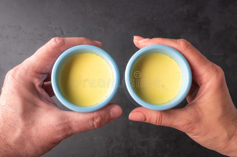 Men`s and women`s hands are hold side by side blue ceramic cups with traditional Indian masala chai tea. Close up top. View selective focus stock photography