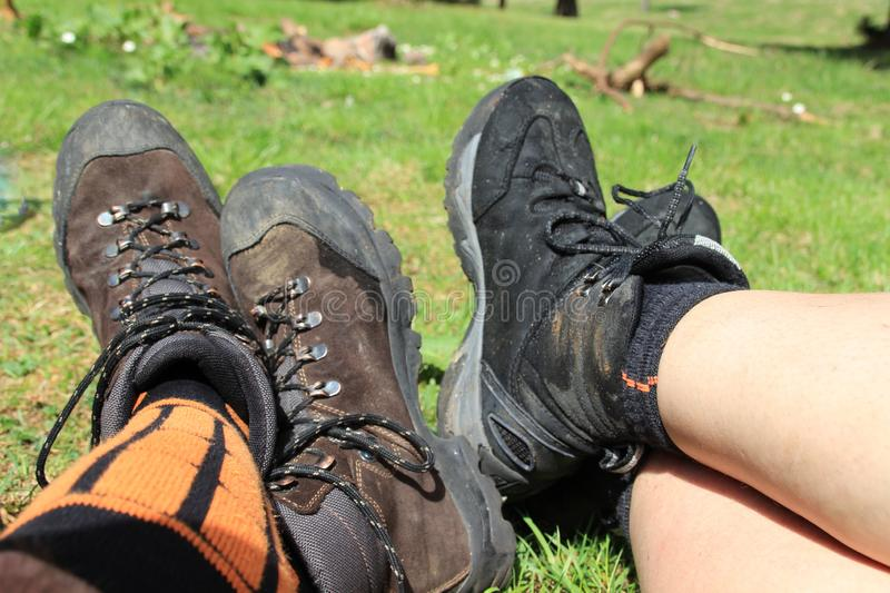 Men`s and women`s trekking shoes on the legs stock photos