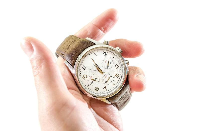 Men`s, wristwatches with brown strap in hand, isolated on white background. Close-up. stock photos