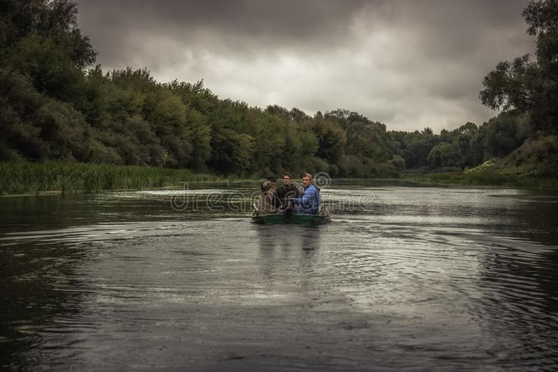 Men sailing on motor boat by river to hunting camp during hunting season in overcast day stock image
