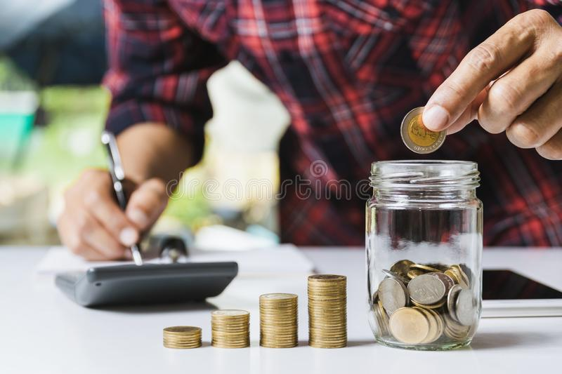 Men are Saint documents about save money and put coin in glass jar also have  calculator, coins on desk. Men are Saint documents about save money and put coin in royalty free stock photography