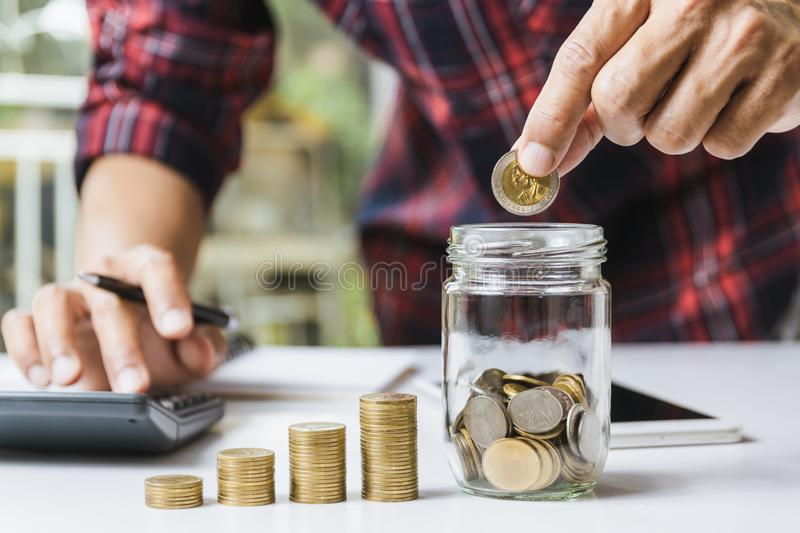 Men are Saint documents about save money and put coin in glass jar also have  calculator, coins on desk. Men are Saint documents about save money and put coin in royalty free stock photos