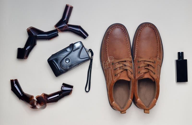 Men& x27; sapatas de couro de s, câmera do filme em um fundo pastel Estilo masculino Olhar do moderno fotos de stock