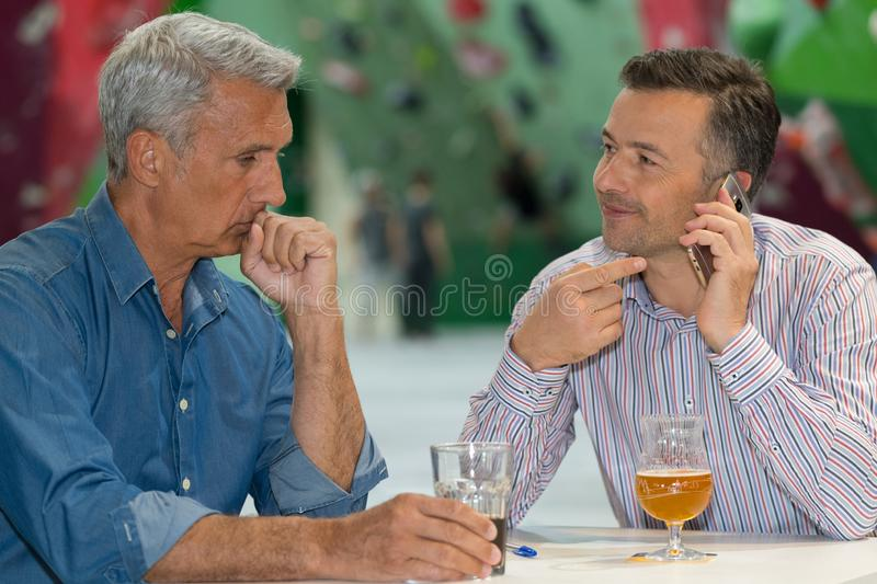 Men sat having drink one talking on telephone royalty free stock photo