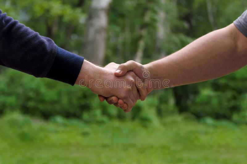 Men shake hands. Businessmen handshaking after good deal. Concept of successful business partnership meeting . Holding hands. Close Up view on green nature royalty free stock image