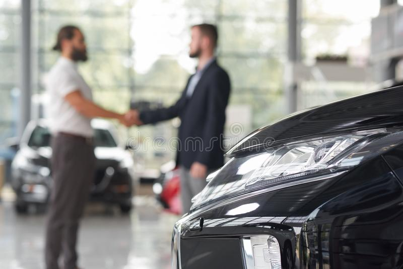 Men shaking hands in modern auto showroom. Automobile headlight and men standing behind. Car dealer and client of car dealership shaking hands. Manager and stock photos