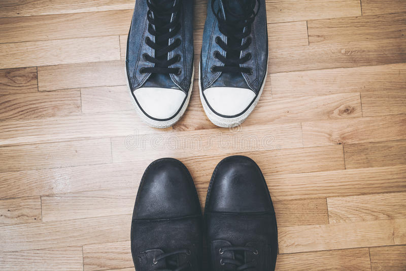 Men shoes and sneakers. Men black leathe shoes and blue worn sneakers on parquet from above stock photo