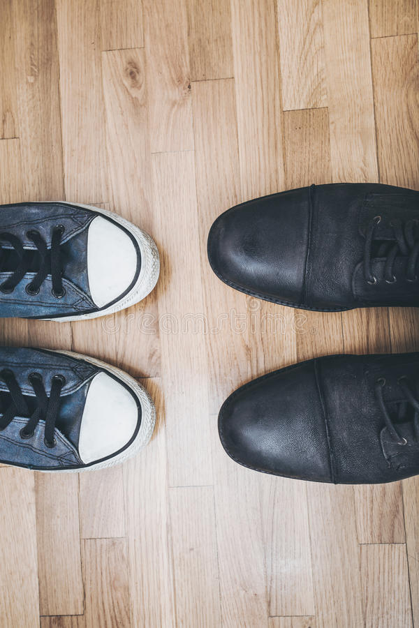 Men shoes and sneakers. Men black leathe shoes and blue worn sneakers on parquet from above royalty free stock images