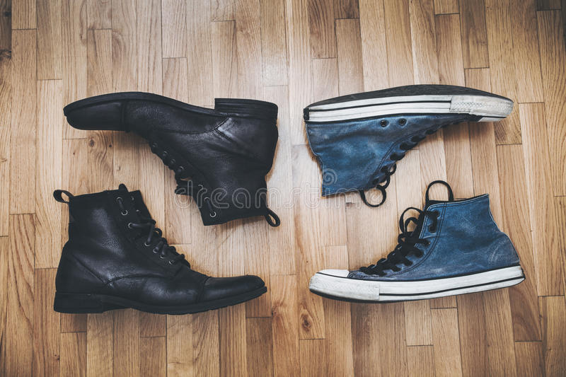 Men shoes and sneakers. Men black leathe shoes and blue worn sneakers on parquet from above royalty free stock photos