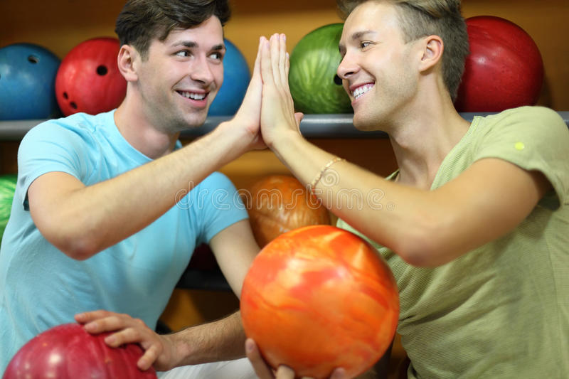 Men sit near shelves with balls in bowling club