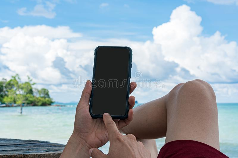 Men sitting on beach chair while using mobile phone royalty free stock photo