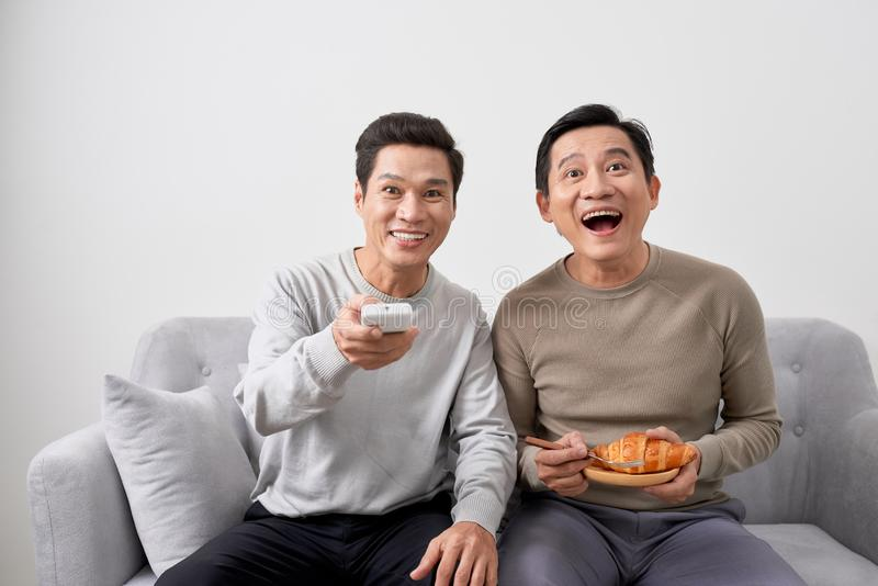 Men sitting on couch watching movie on television together at home stock photos