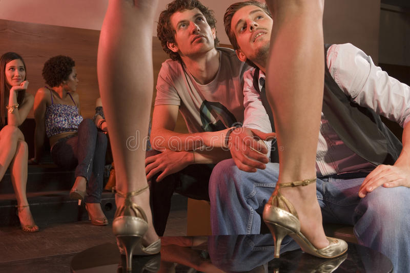 Men sitting in a nightclub, looking up at a woman dancing on a table. royalty free stock images