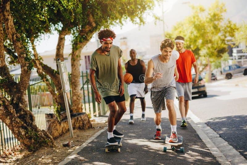 Men skating on skateboard on pavement. Two men skating on skateboard on a pavement while their mates cheer them. Basketball guys walking on pavement using royalty free stock images