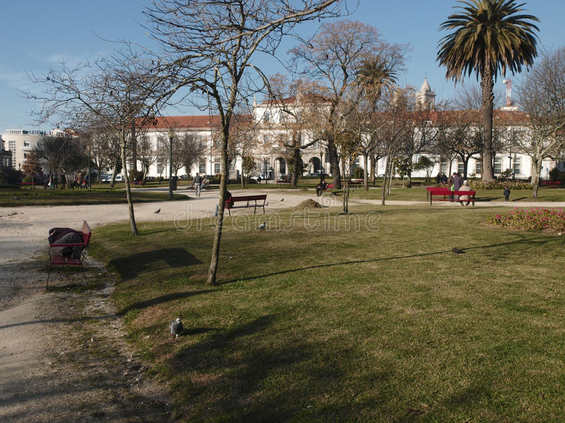 Men sleep on bench on city gardens. Usual scenery on a sunny day on Praça da Republica gardens at portuguese city Porto royalty free stock photos