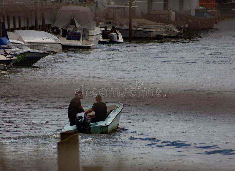 Men in small boats who walk along the siles to get to the lagoon and then to Venice stock photo