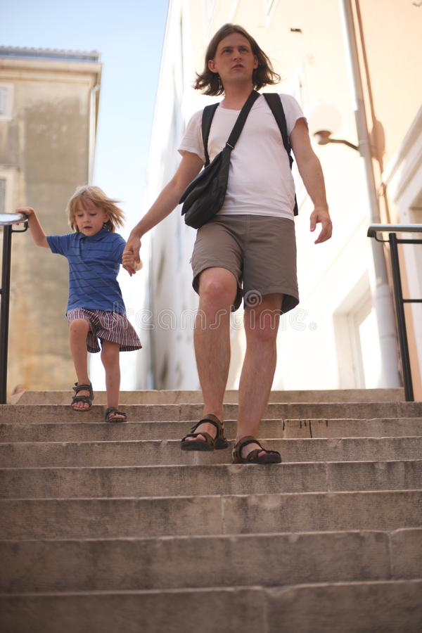 A man with a small son in the street stock photography