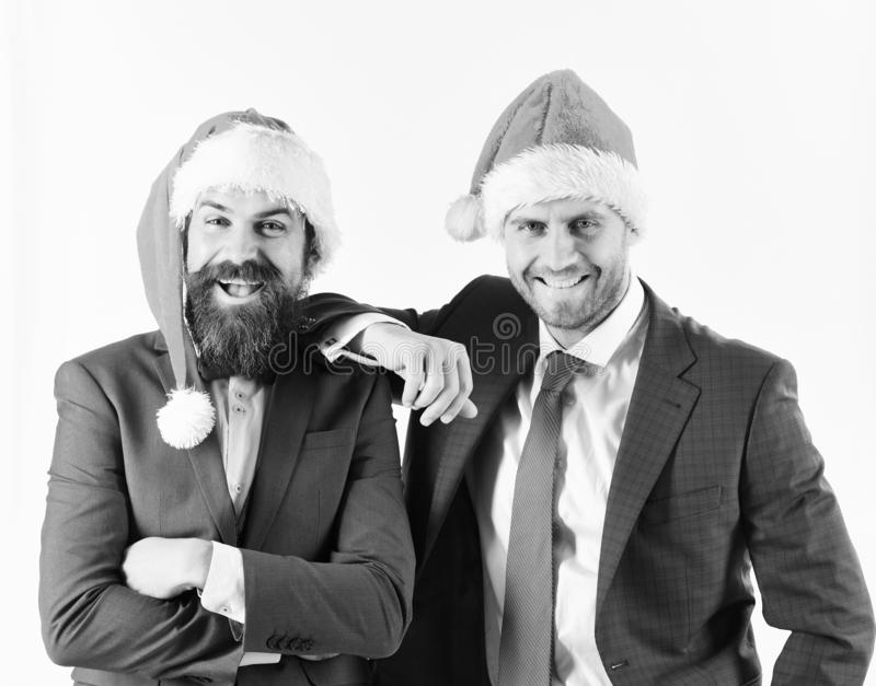 Men in smart suits and Santa hats on white background stock photo