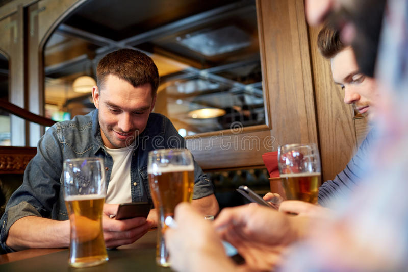 Men with smartphones drinking beer at bar or pub. People, men, leisure, friendship and communication concept - male friends with smartphones drinking draft beer royalty free stock photos