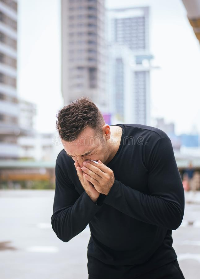 Man sneeze on street because pollution,Male got nose allergy on street stock photography