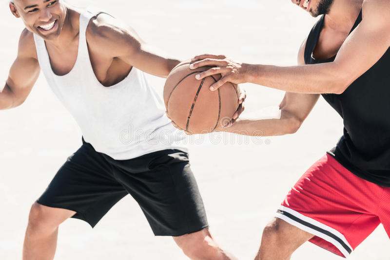Men in sportswear playing basketball together stock photography