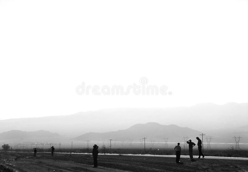 Men staring off into distance. Men looking off into the far distance along a road with power lines and desert mountains in background royalty free stock images