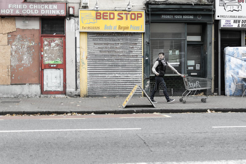Men on the street with supermarket trolley. ENGLAND, BRISTOL - 19 OCT 2015: Men on the street with supermarket trolley royalty free stock images