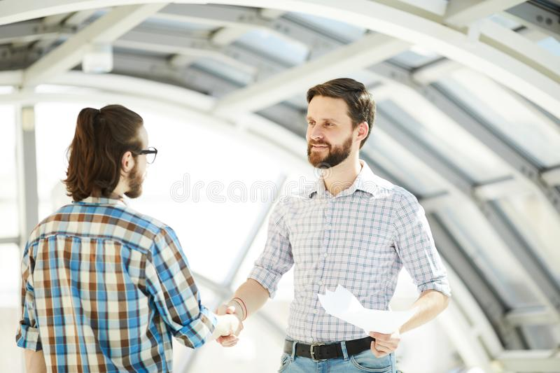 Men striking deal. Two contemporary financiers handshaking to express striking deal after negotiation royalty free stock image