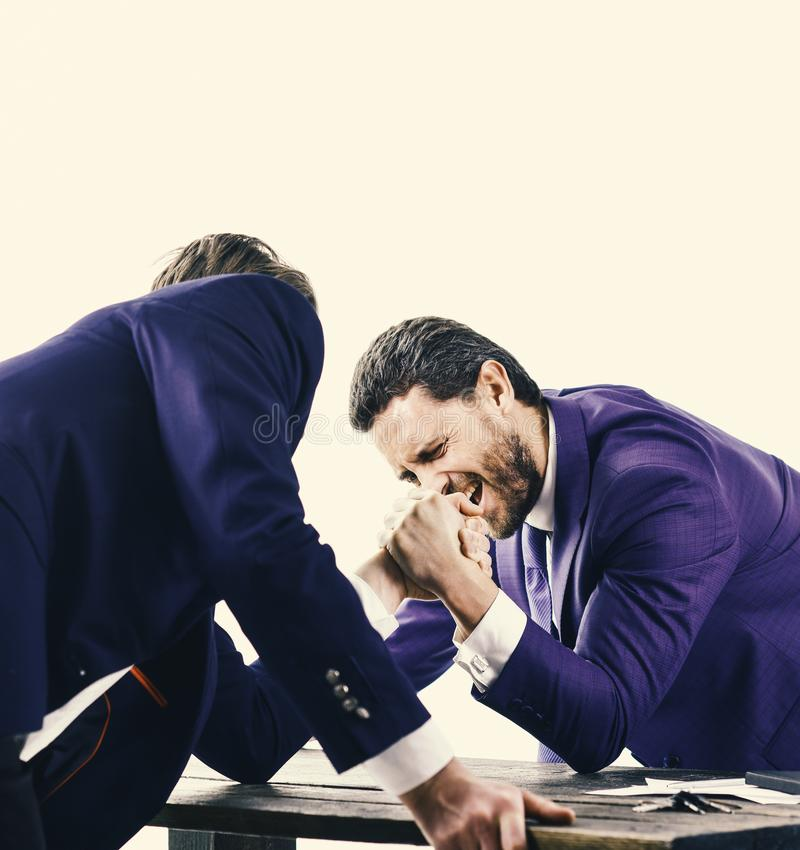 Men in suit or businessmen with screaming face compete in armwrestling on table on white background. Winner and defeated. Concept. Confrontation of business royalty free stock photo