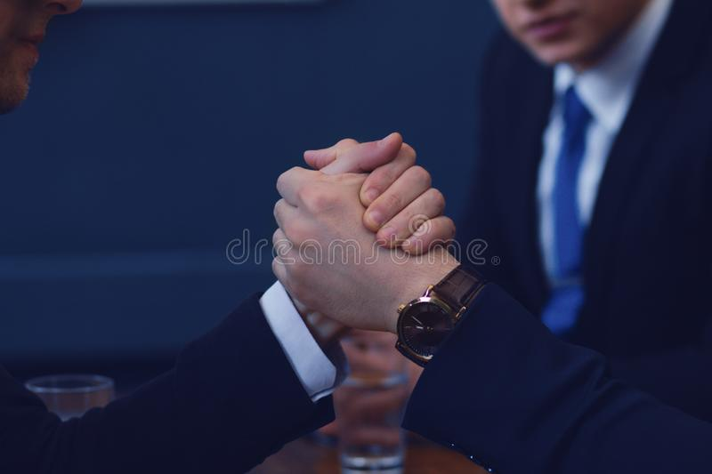 Business armwrestling in office. Men in suit or businessmen with tense faces compete in armwrestling on table on dark background stock photography