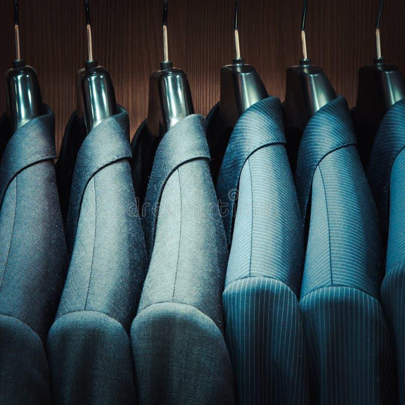Men suit jackets. Row of men suit jackets in apparel store stock photo