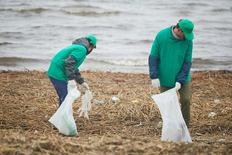 Men taking rubbish on coast. Two men in green uniform standing and picking litter on coast royalty free stock photo